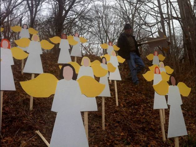 Art teacher Eric Mueller sets up 27 wooden angel cut-outs in memory of the victims of the elementary school shooting in Newtown, Conn.  Photo Credit: Yamiche Alcindor, USA TODAY