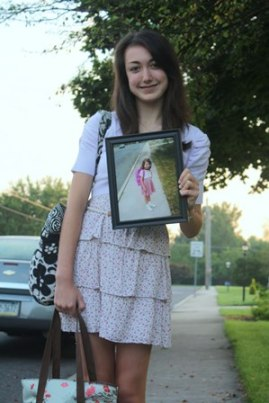 First day of school, senior year, my daughter holds a photo of her first day of kindergarten...